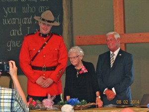 Mary Agnes standing at head table with Constable Pankratz and Mayor Armitage