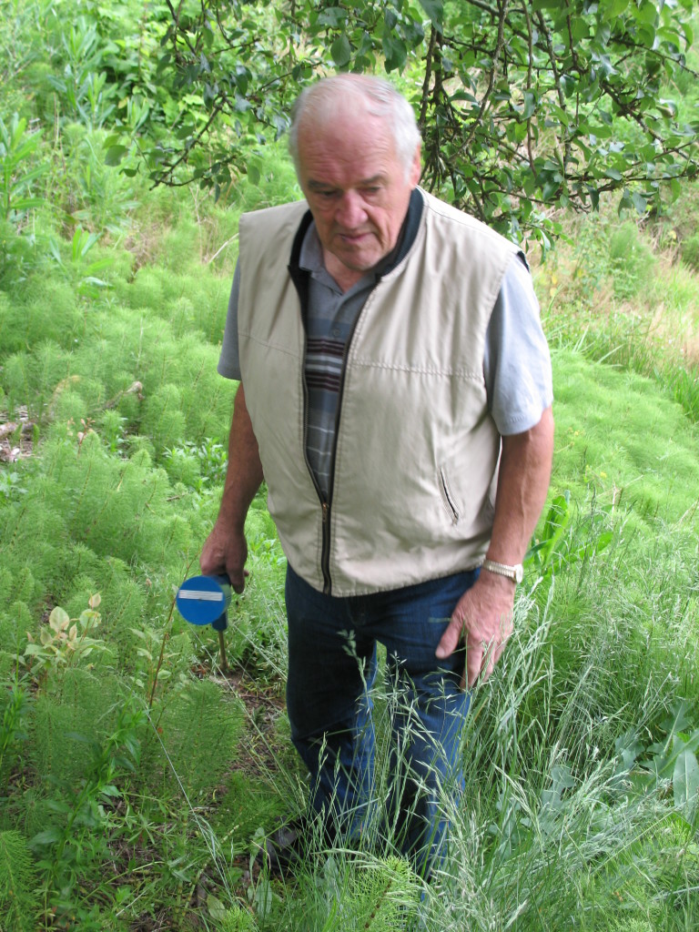 Joe Cindrich holding a syringe & searching for Japanese Knotweed