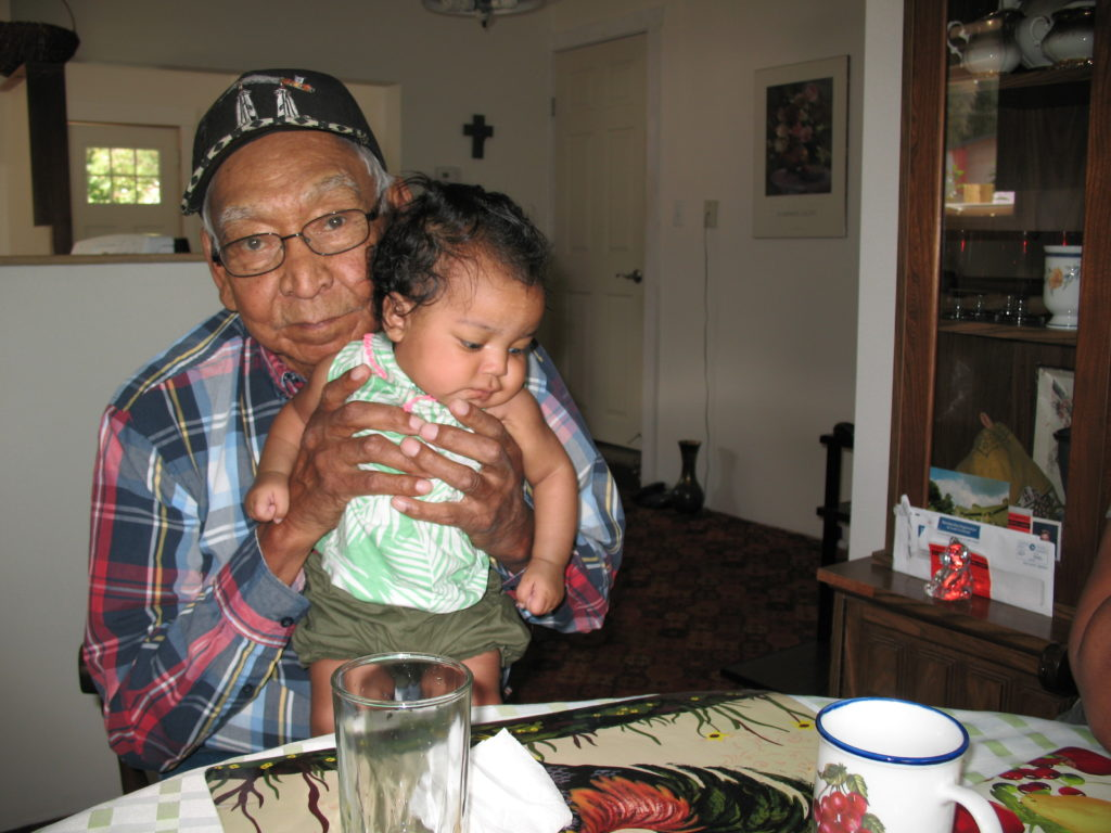 Elder John Terbasket, holding his great granddaughter.